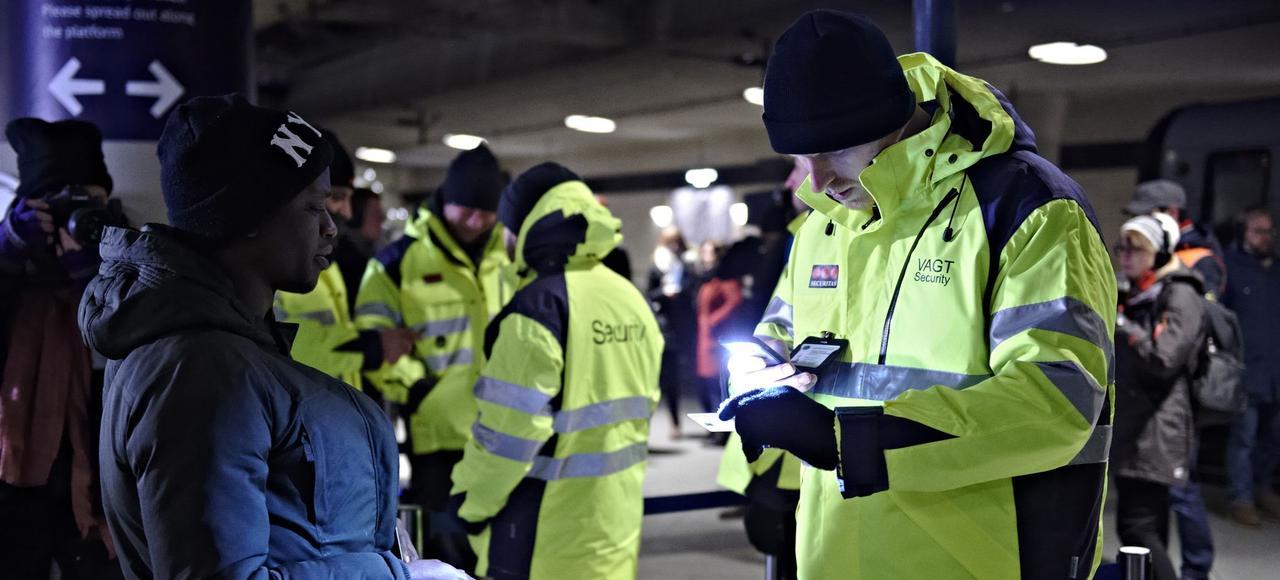Des vigiles vérifient les cartes d'identité des passagers pour prévenir l'entrée de migrants illégaux en Suède, lundi à la gare ferroviaire de l'aéroport de Kastrup, au Danemark, près de la frontière entre les deux pays.