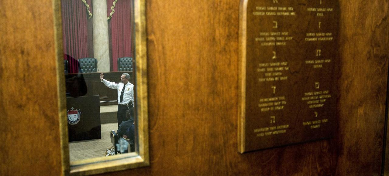 Vue d'une salle de cours de l'université Liberty, à travers une porte sur laquelle est apposée une plaque des Dix commandements.