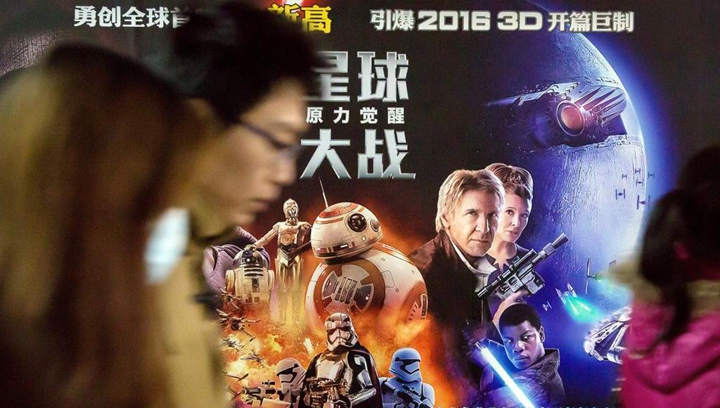 Des passants devant l'affiche de <i>Star Wars VII - The Force Awakens</i>, à Shanghaï.