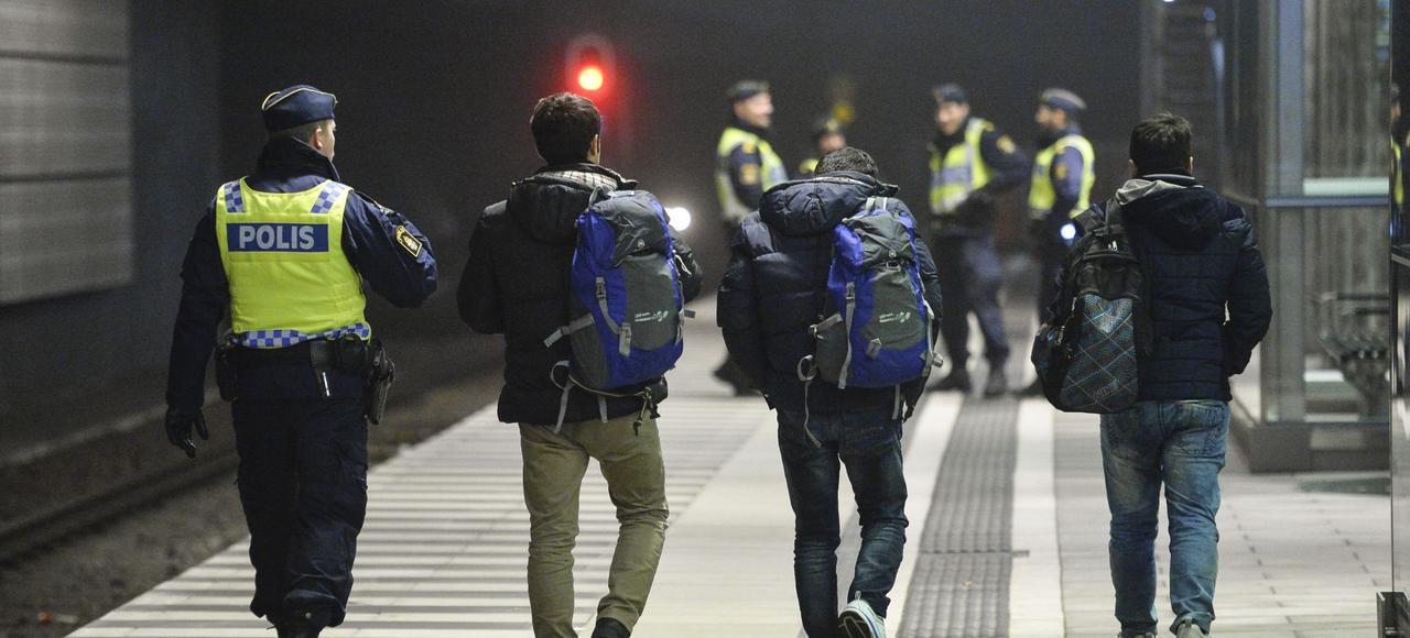 Gare de Hyllie, à Malmö. Trois migrants arrivés par un train sont escortés, en décembre, par un policier suédois.