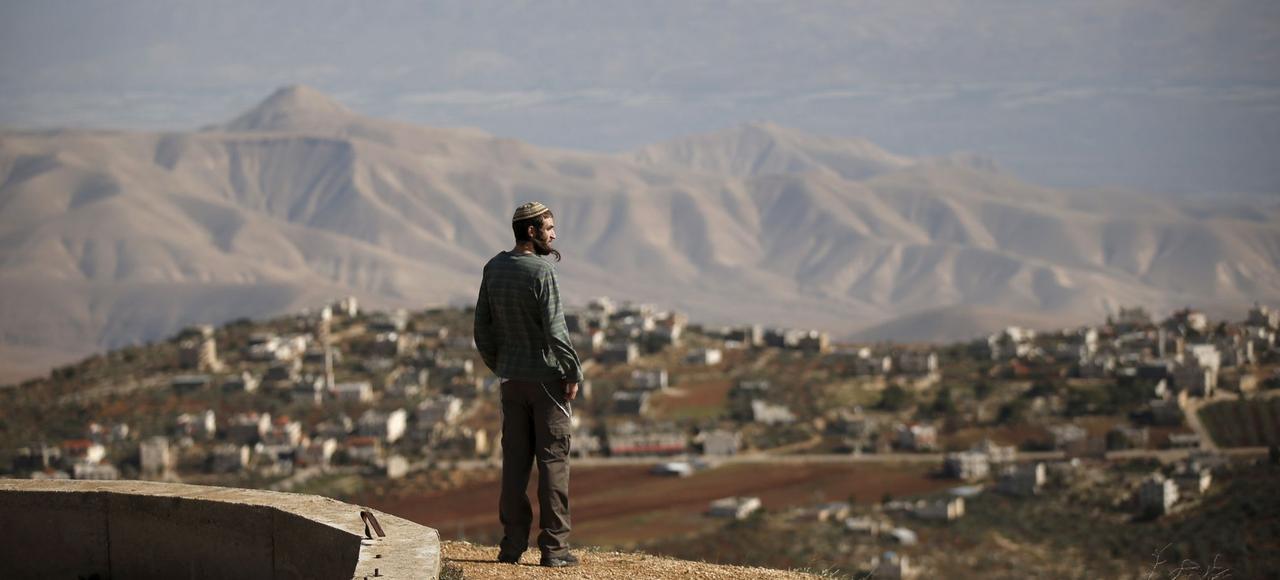 Un jeune colon israélien domine le village de Douma, depuis l'avant-poste de Yishuv Hadaat, une colonie de peuplement non autorisée, perchée sur une colline du nord de la Cisjordanie