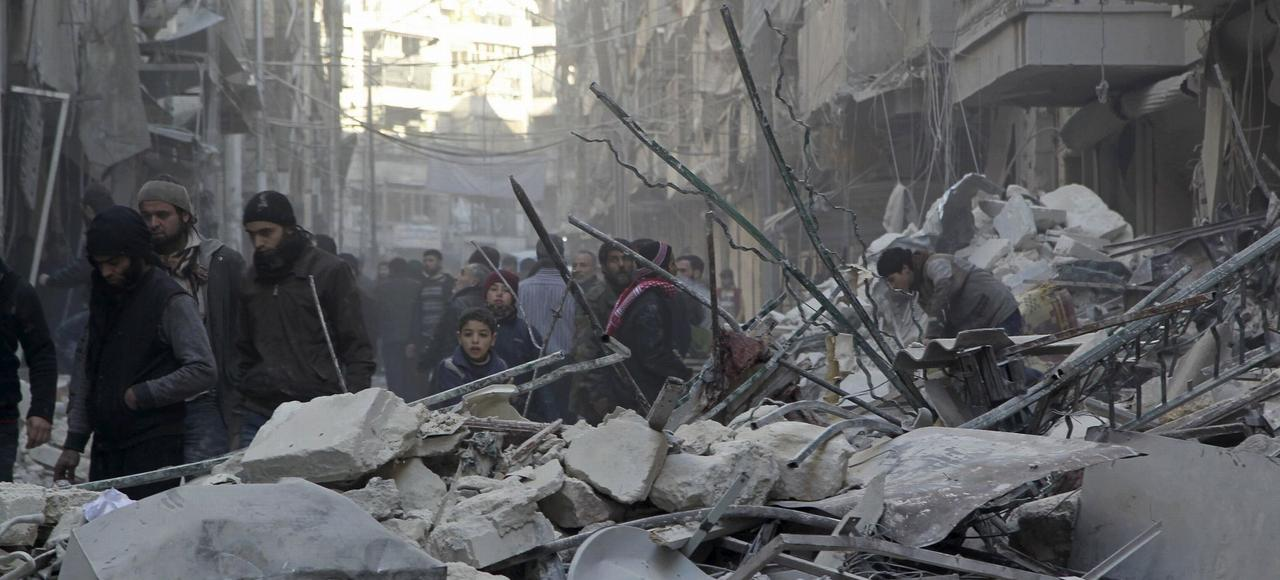 Des habitants d'al-Chaar, quartier rebelle d'Alep, traversent les décombres après un bombardement de l'armée syrienne, le 4 février.