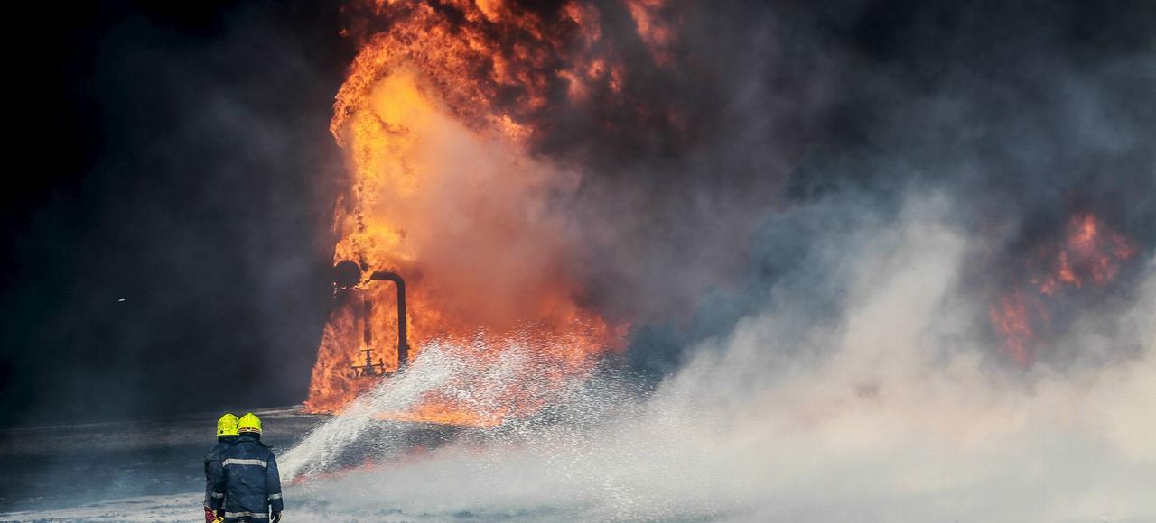 Des pompiers tentent d'éteindre l'incendie d'un réservoir de pétole dans le port de Ras Lanouf, en Libye, le 6 janvier après que les terroristes de Daech ont attaqué les ports pétroliers de Sidra et de Ras Lanouf.