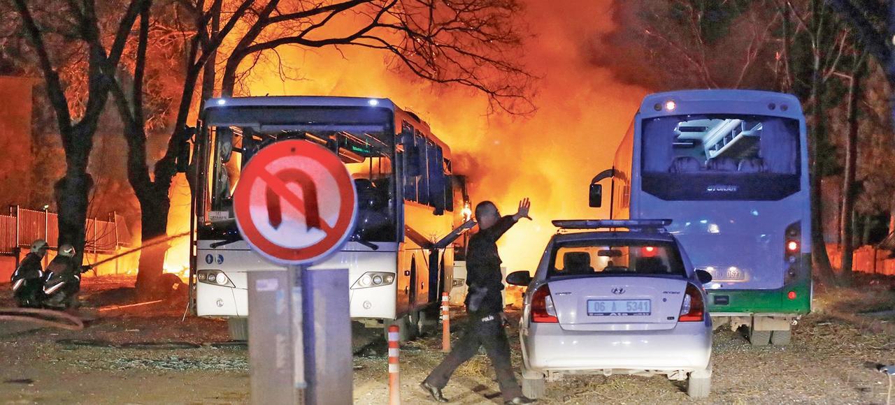 Un policier arrive sur le lieu de l'attentat à la voiture piégée alors que les pompiers tentent d'éteindre les flammes, mercredi, à Ankara.