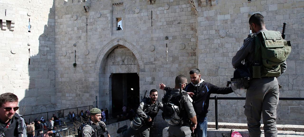 Des policiers israéliens fouillent un Palestinien devant la porte de Damas, vendredi, à Jérusalem.