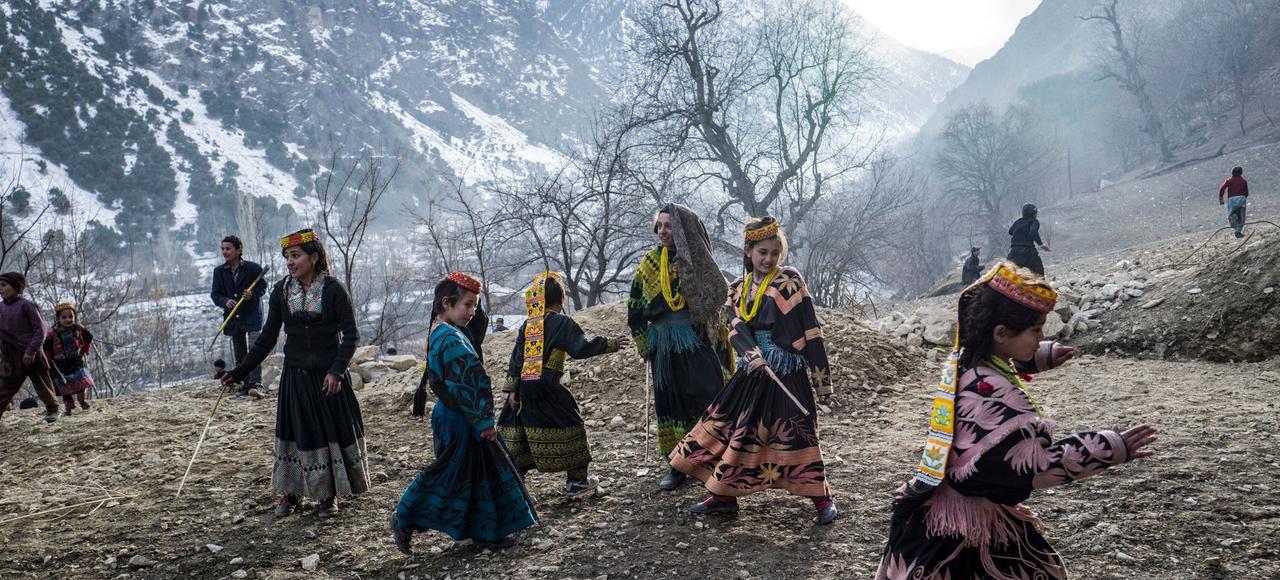 Face au soleil couchant, des jeunes filles kalash vêtues de la robe et de la coiffe (shushute) traditionnelles jouent aux abords de Brun, village de la vallée de Bumburet.