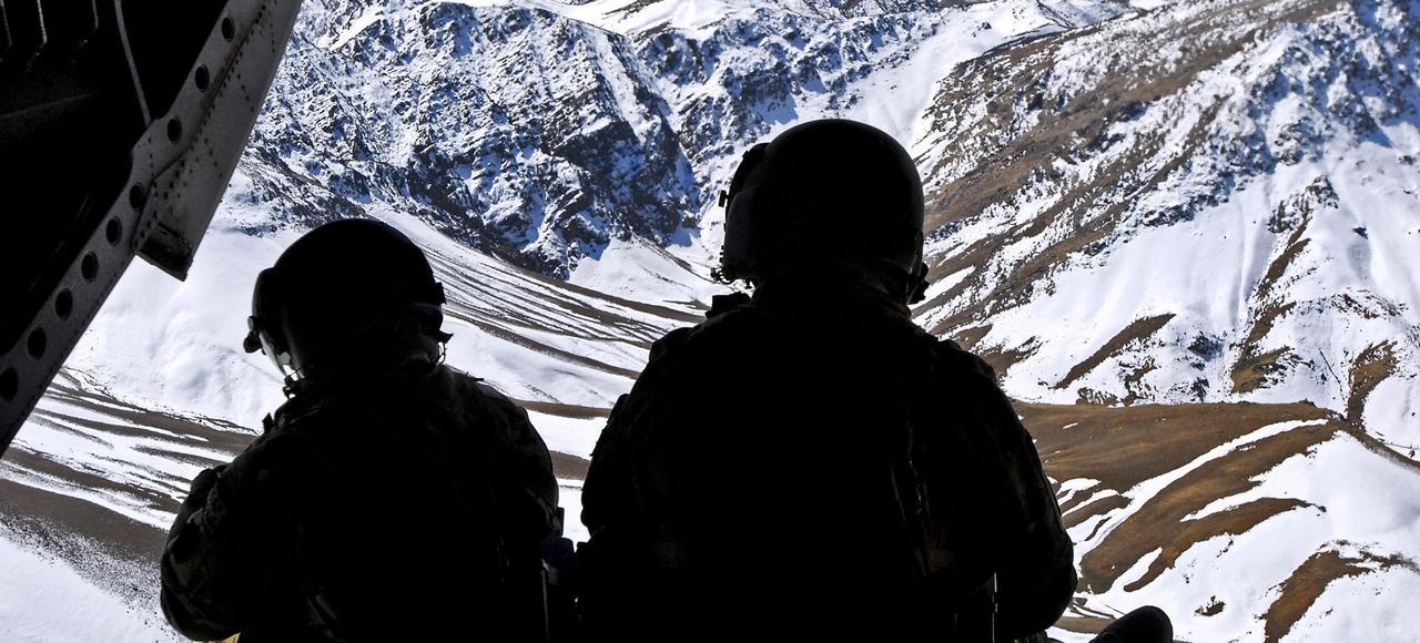 À bord d'un hélicoptère de transport lourd CH-47 Chinook, deux membres d'équipage observent les montagnes de l'Oruzgan, en Afghanistan.