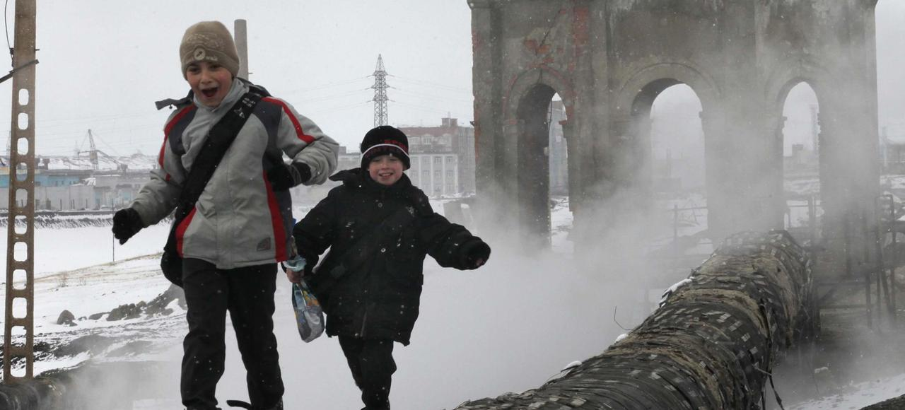En mai 2010, des enfants jouent dans un quartier de Norilsk, enveloppée de nappes de brouillard dues aux rejets de l'usine historique de la ville.