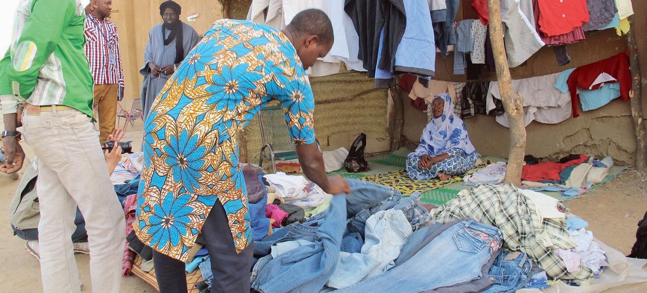 À Gao, Nana Sidibé Cissé, assise dans sa friperie acquise grâce à une aide de l'OIM, attend le client.«Les gens sont revenus. Les déplacés, les réfugiés, chaque jour de nouvelles personnes sont de retour», témoigne cette femme de 57 ans qui a regagné Bamako en janvier 2014.