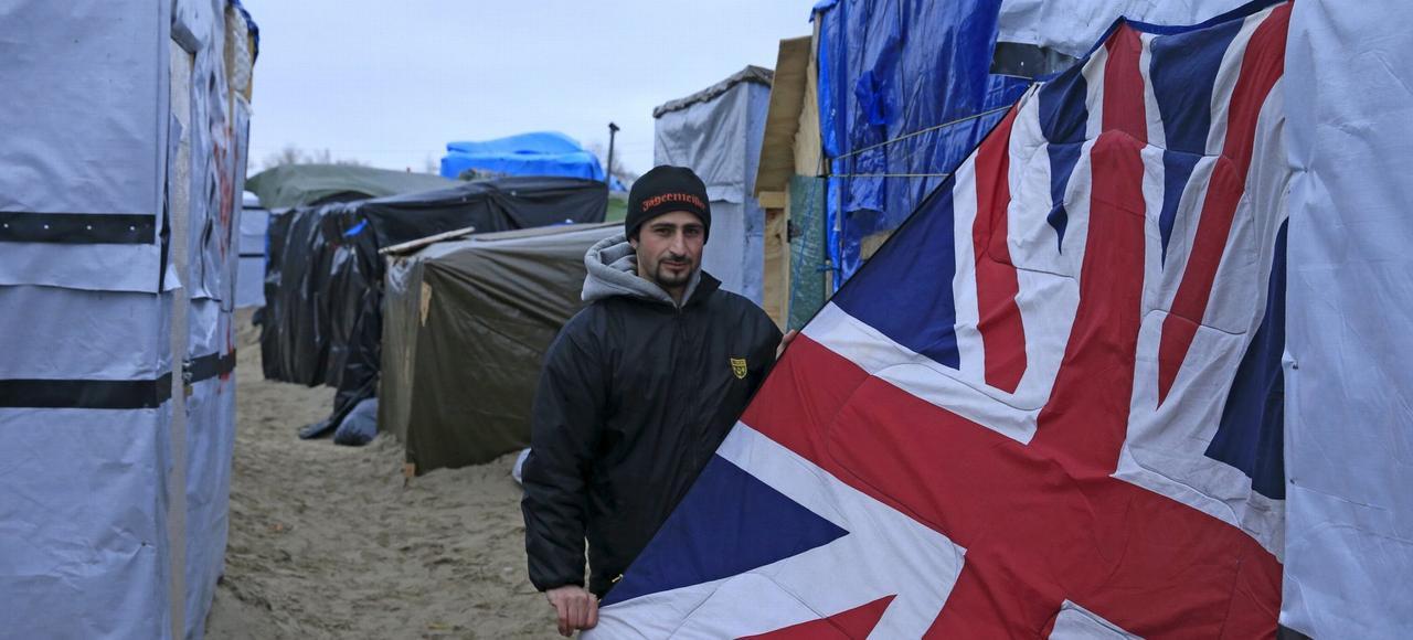 Un migrant syrien montre l'Union Jack, le drapeau britannique qui lui sert de porte dans son abri de la «jungle» de Calais.