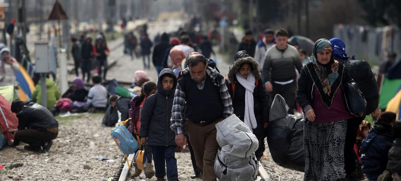 Des réfugiés longent la voie ferrée, près du village d'Idomeni jeudi, dans l'espoir de passer la frontière.