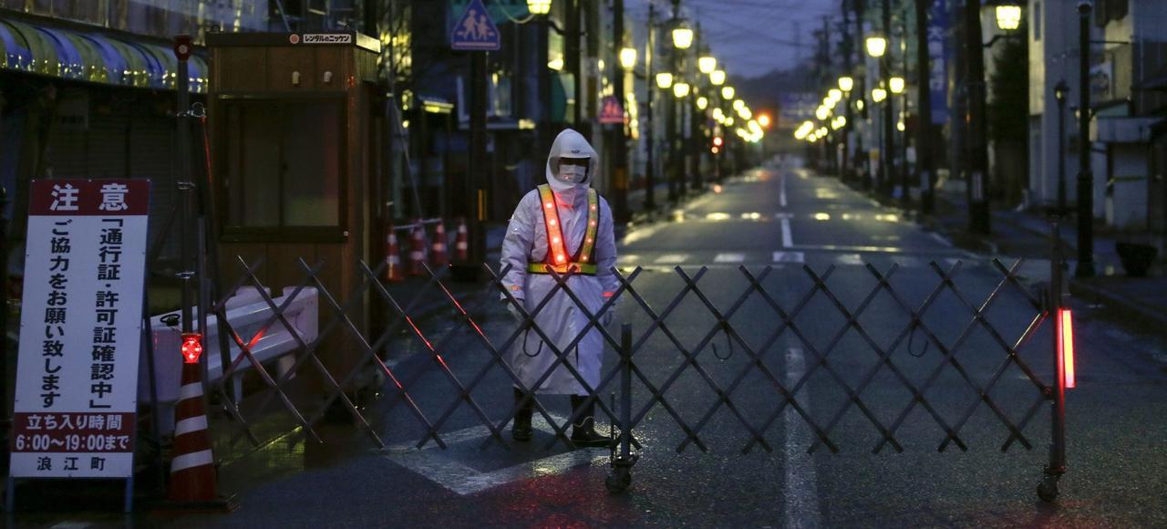 Un gardien interdit l'accès à la ville de Namie, située en pleine zone sinistrée, au nord de la centrale nucléaire de Fukushima Daiichi, mercredi.
