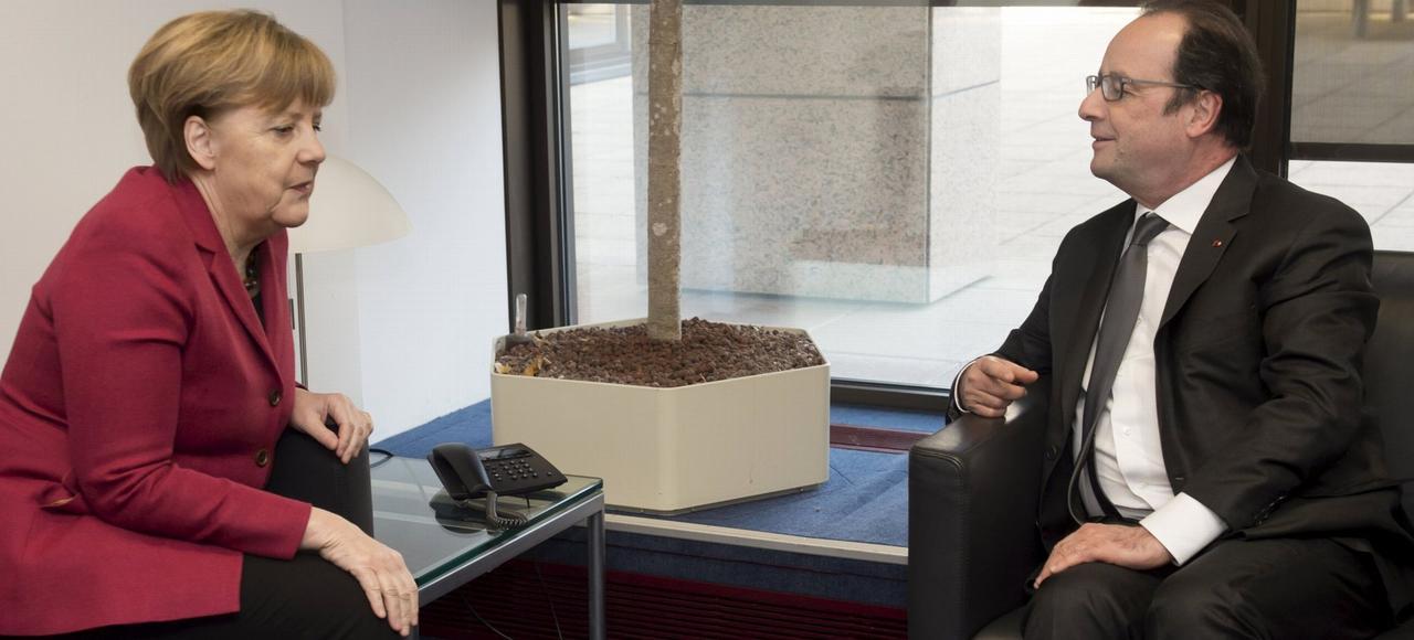 Angela Merkel s'entretient avec François Hollande en marge d'un sommet européen, le 17 mars à Bruxelles.