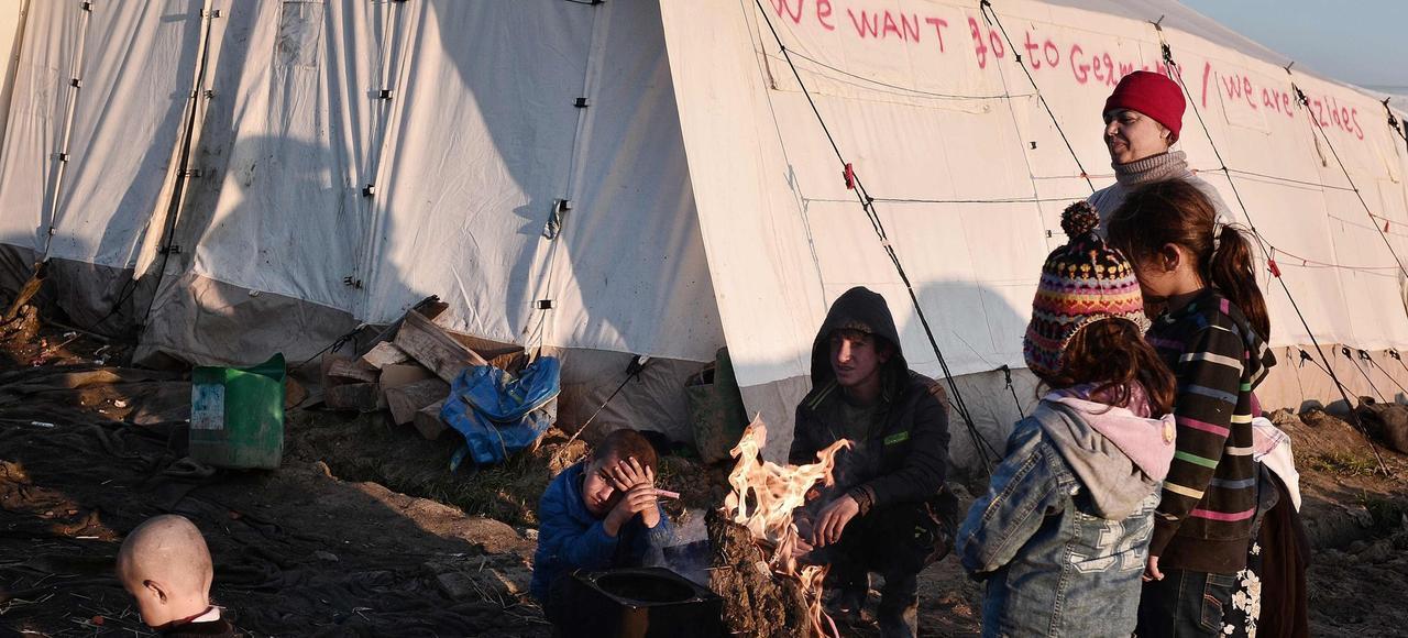 Une famille de réfugiés yazidis d'Irak se réchauffe autour d'un feu, dimanche dans le camp grec d'Idomeni, à la frontière avec la Macédoine