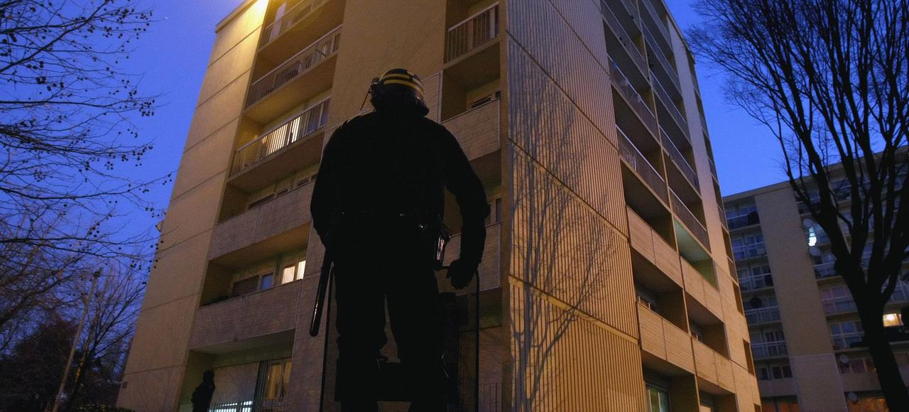 Un policier au pied d'une tour à Villiers-le-Bel, dans le Val d'Oise, au lendemain des émeutes de 2007.