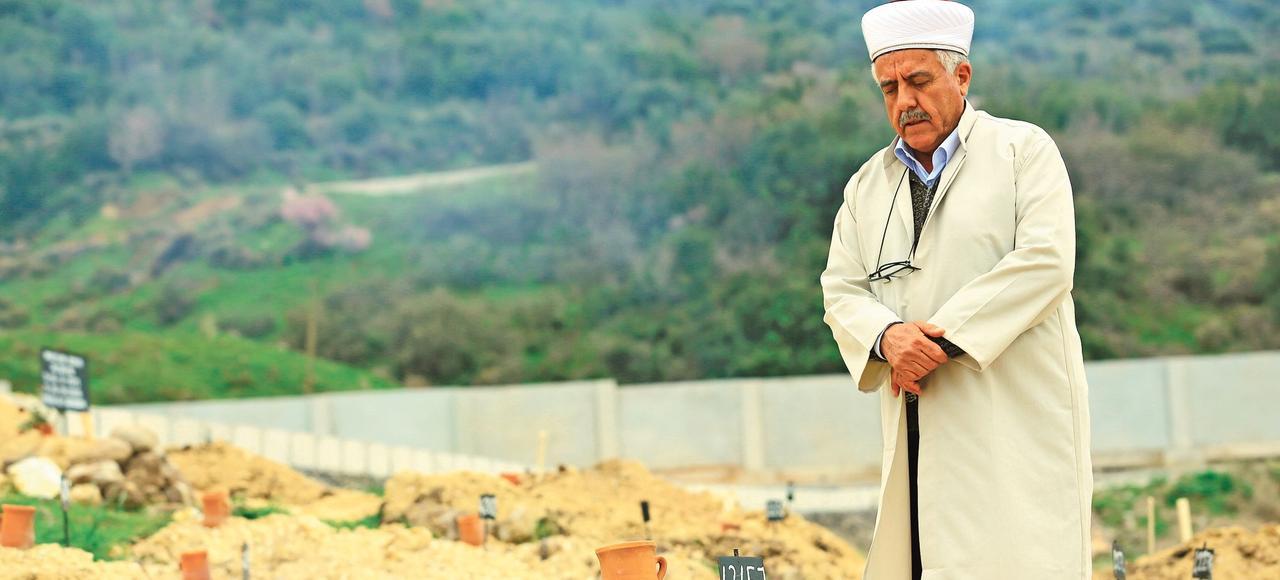 Ahmet Altan, l'imam du cimetière des Anonymes, à Izmir, prie devant les sépultures de migrants non identifiés ayant perdu la vie en tentant de rejoindre clandestinement la Grèce en bateau.