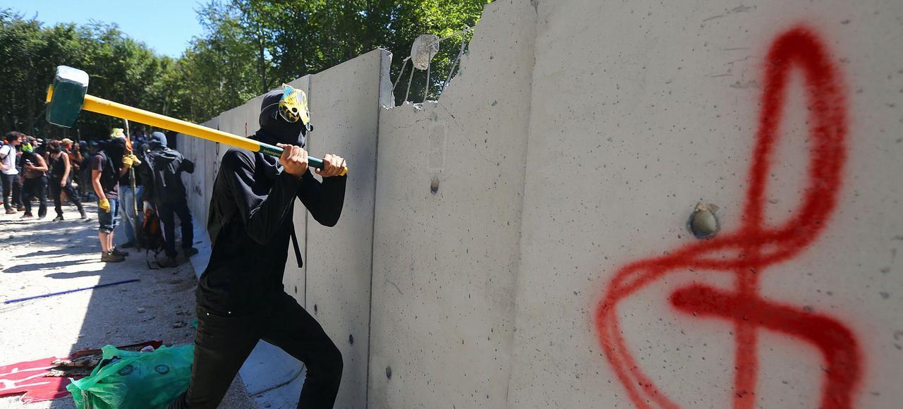 Un opposant au projet de stockage de Bure s'attaque au mur d'enceinte du site d'enfouissement, le 14 août.