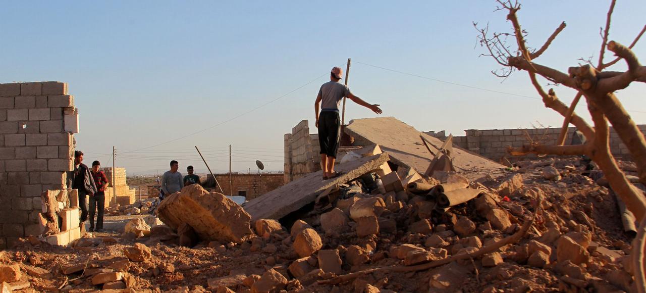 Des civils constatent, lundi, les destructions après les attaques aériennes qui ont fait plusieurs morts dans le village rebelle d'Owaijel, à l'ouest d'Alep.