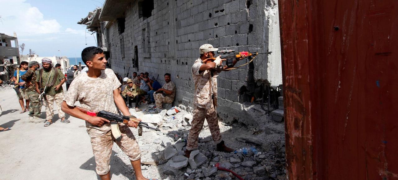 Les forces libyennes alliées au gouvernement U.N. visent leur arme vers les soldats de l'État islamique récalcitrants, en première ligne des combats dans la région de Cambo, à Syrte le 19 octobre 2016.