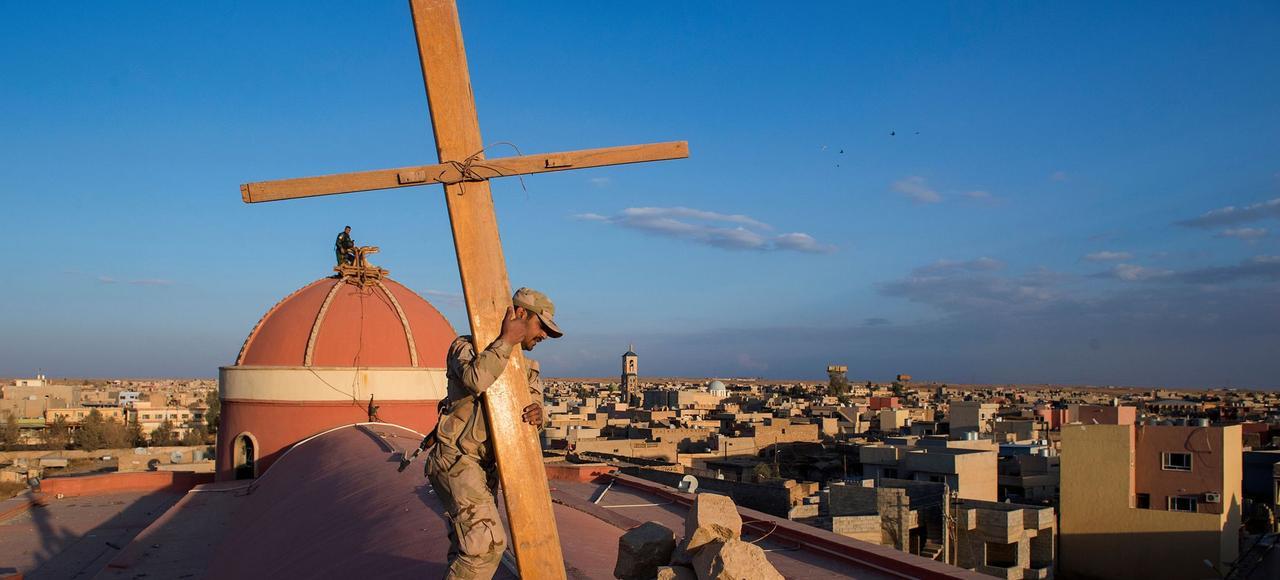 A Qaraqosh, sur le toit de la cathédrale de l'Immaculé Conception, la plus grande église catholique du Moyen-Orient entièrement ravagée par le feu et saccagée, deux soldats de la N.P.U (Nineveh Plain Protection Units) réinstallent une croix de bois sur le dôme en lieu et place de l'ancienne détruite par les djihadistes de Daech (Etat Islamique).