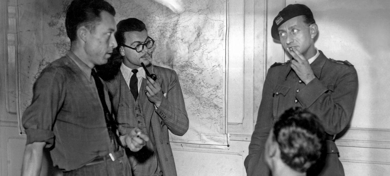 Albert Camus (à gauche) avec Jacques Baumel (lunettes) et André Malraux (debout, àdroite) dans les locaux du journal <i>Combat</i> le21septembre 1944.