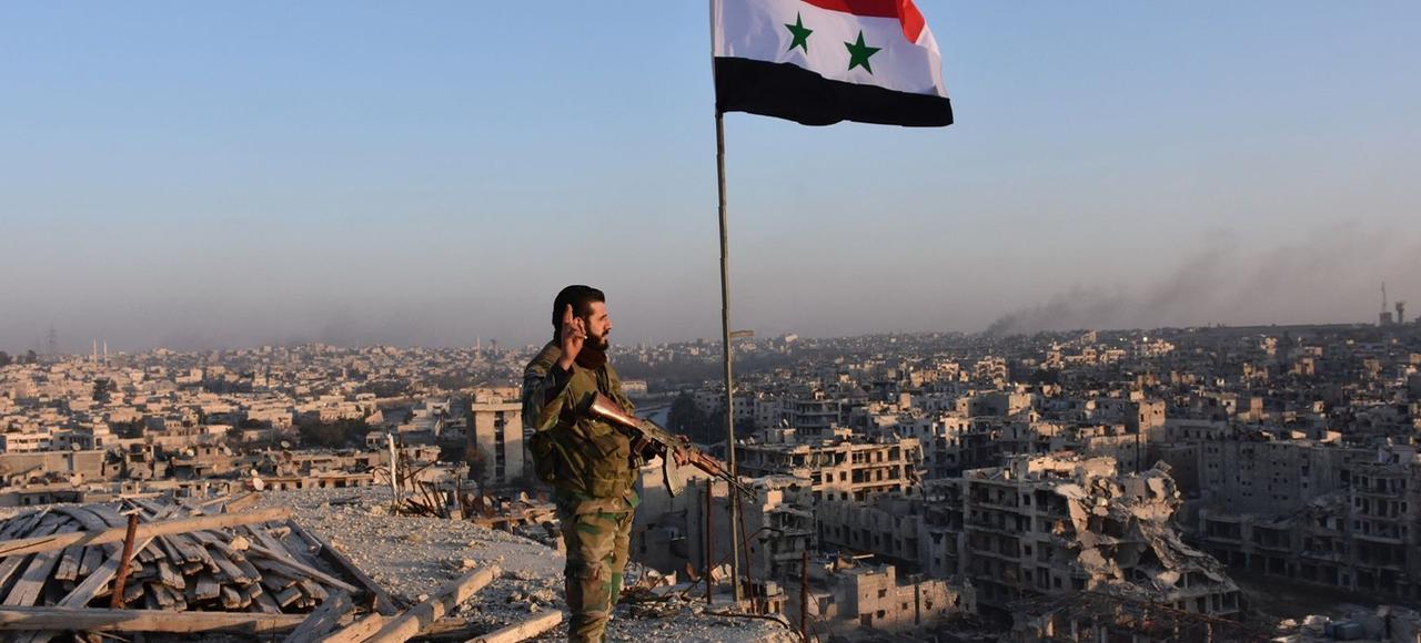 Un soldat syrien pro-gouvernement observe, le 28 novembre, la ville d'Alep et ses faubourgs depuis le haut d'un immeuble.
