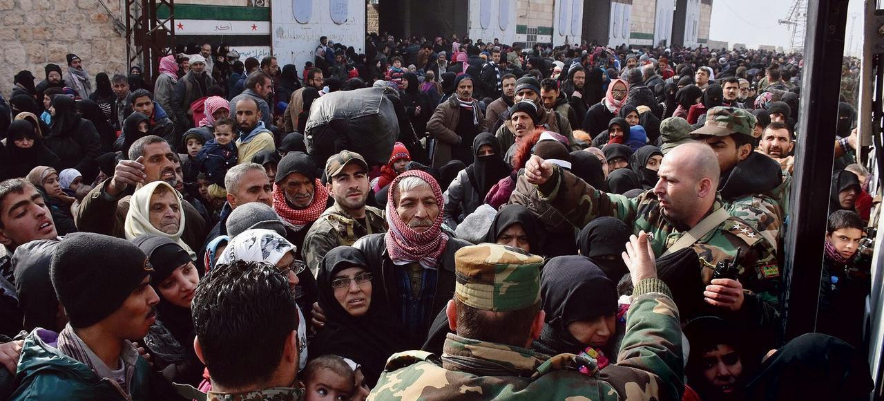 Des familles attendant de monter dans un bus affrété par le gouvernement pour fuir Alep, mardi.