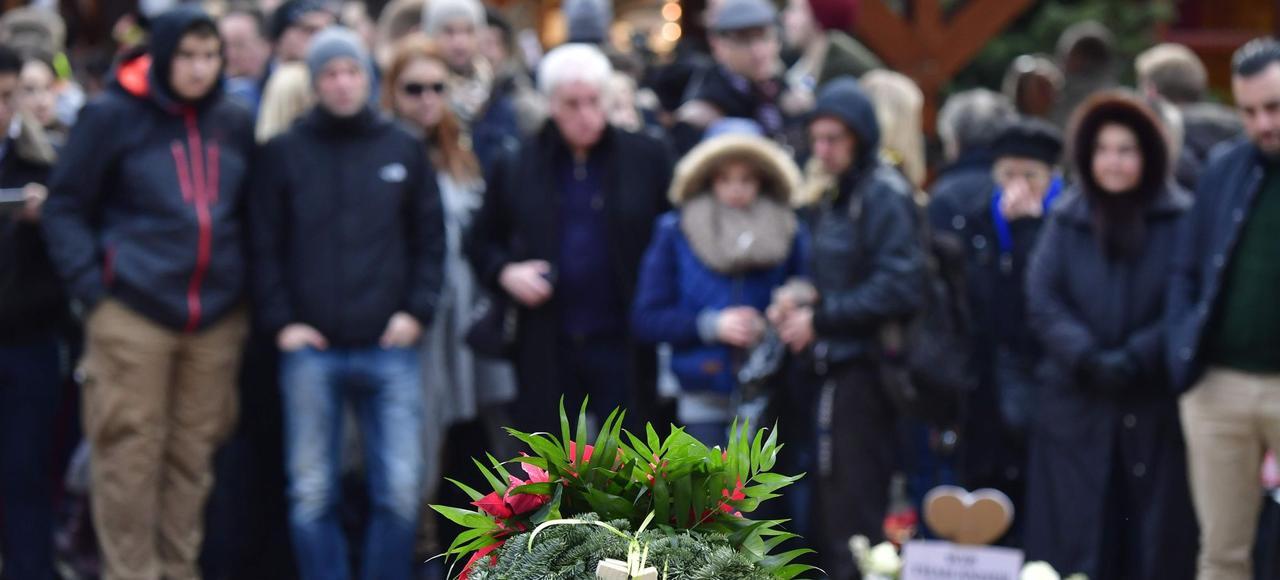 Des personnes se recueillent, samedi, à Berlin, devant le mémorial improviséen hommage aux victimes de l'attentat au camion-bélier.
