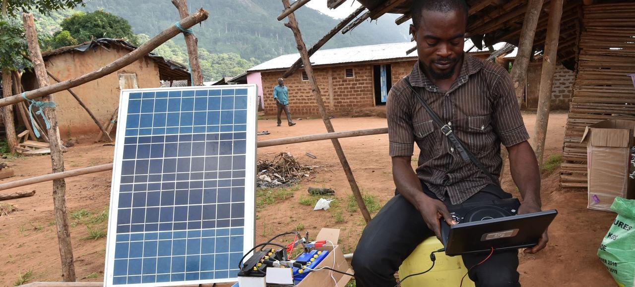 Un homme utilise l'énergie solaire dans un village sans électricité, en Côte d'Ivoire.