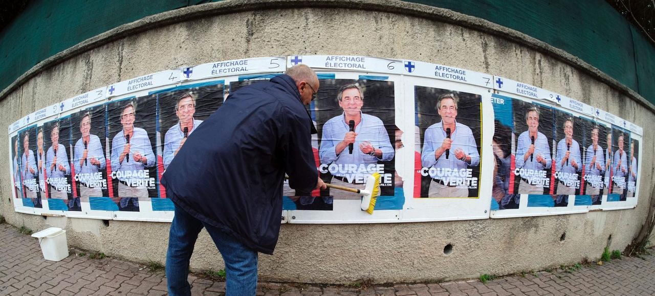 Un militant LR colle des affiches de campagne de François Fillon, à Marseille.