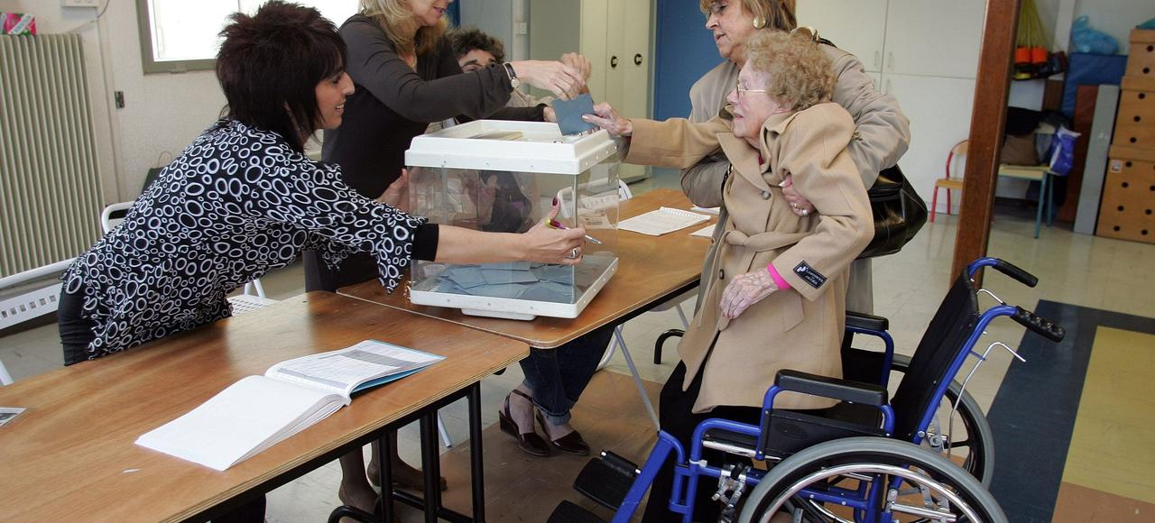Une personne en fauteuil roulant s'apprête à voter.