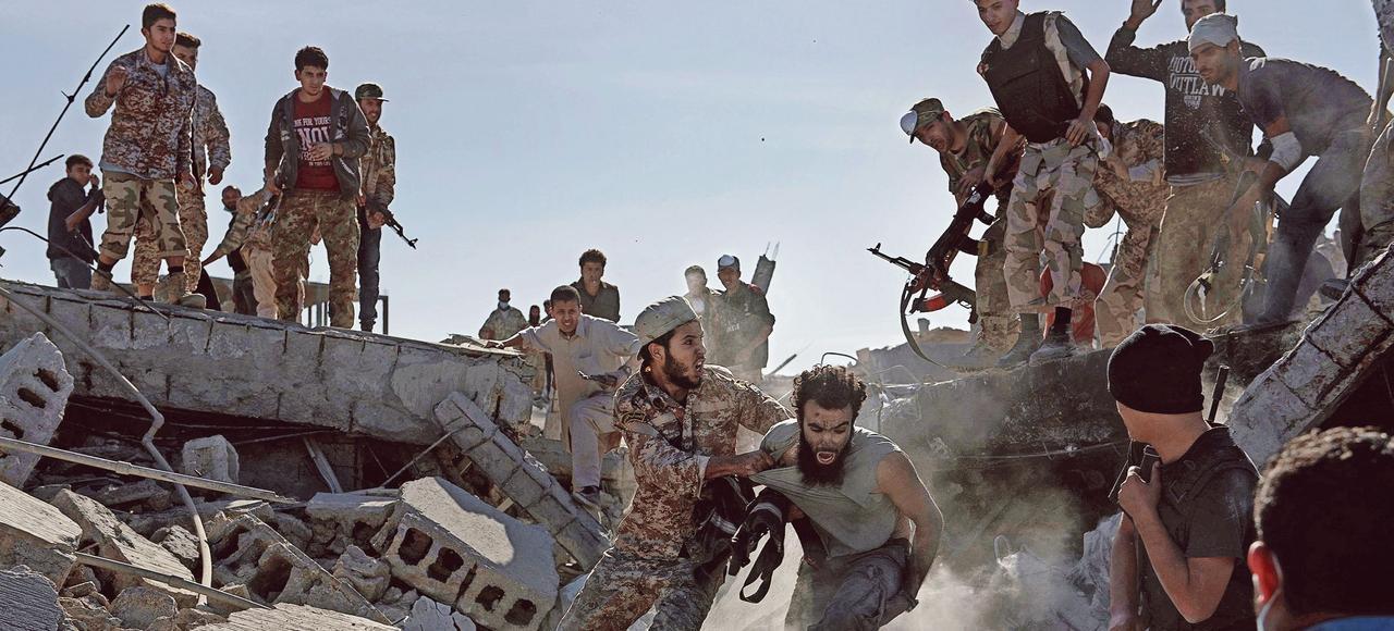 Un combattant de Daech <i>(à droite)</i>, qui venait de se rendre, est violemment traîné par un soldat libyen affilié au gouvernement de Tripoli, le 5 décembre dernier. Quelques minutes plus tard, le corps du djihadiste sera retrouvé criblé de balles.