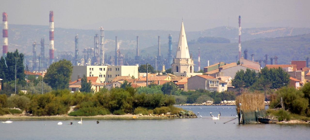 Le village de Berre (Bouches-du-Rhône) avec la lagune en premier plan et les usines petrochimiques en arrière plan.