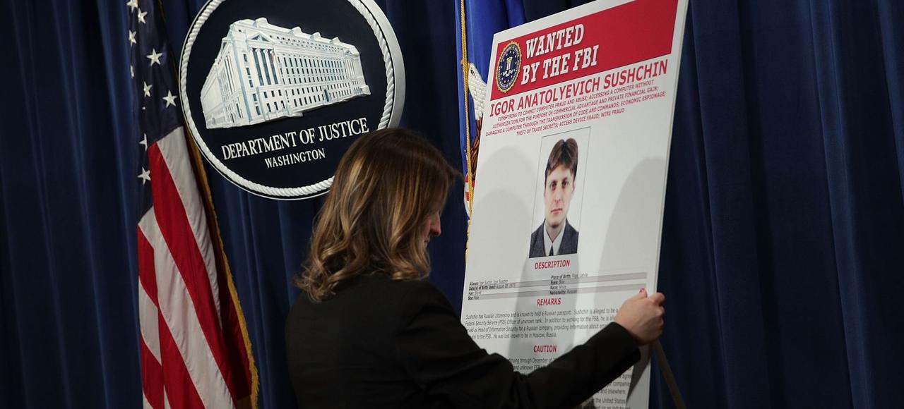 Une employée du ministère de la Justice américaine installe un avis de recherche pour Igor Souchtchine, un agent du FSB, avant une conférence de presse, mercredi, à Washington