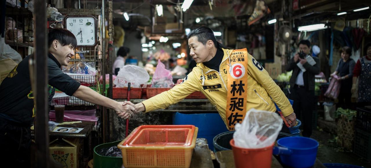Freddy Lim, leader du Parti du nouveau pouvoir, salue des commerçants sur un marché, à Taïpeh, pendant la campagne présidentielle taïwanaise, en janvier 2016.