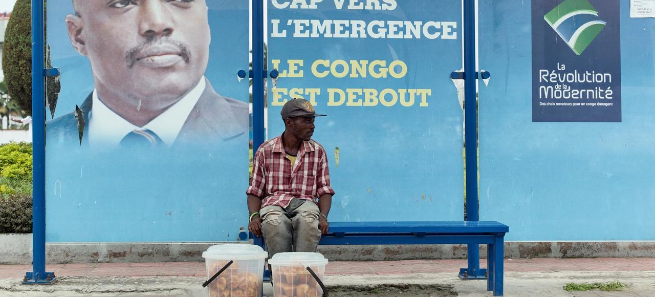 Un vendeur attend son bus dans la capitale. Derrière lui, le portrait du président, Joseph Kabila.