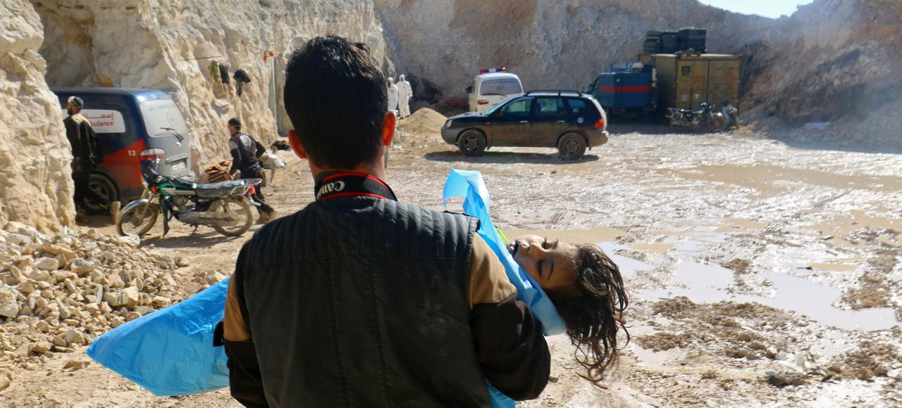 Un homme évacue un enfant mort après l'attaque aérienne du 4 avril dans le village de Khan Cheikhoun.