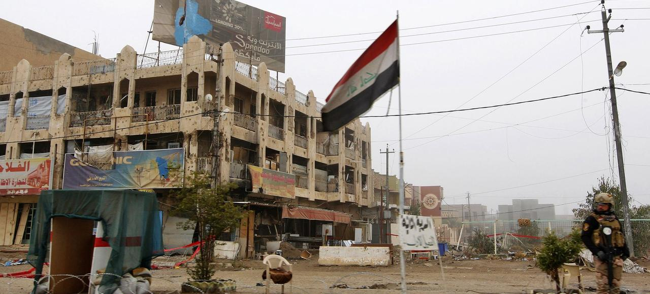 Un policier irakien patrouille dans un quartier en ruines de Faloudja, en décembre 2016, six mois après la reconquête de la ville par les forces gouvernementales.