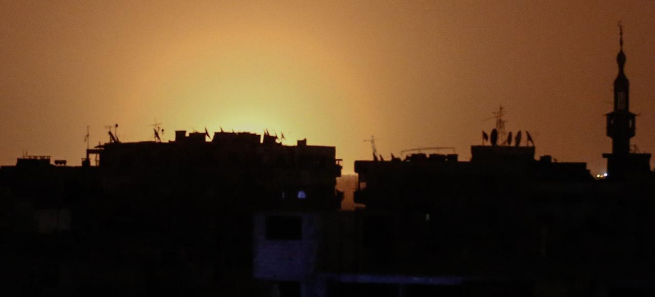 Photo prise depuis la ville de Douma, tenue par les rebelles, montrant des flammes s'élevant près de l'aéroport international de Damas. Un site militaire syrien proche de l'aéroport a été bombardé ce jeudi au petit matin.