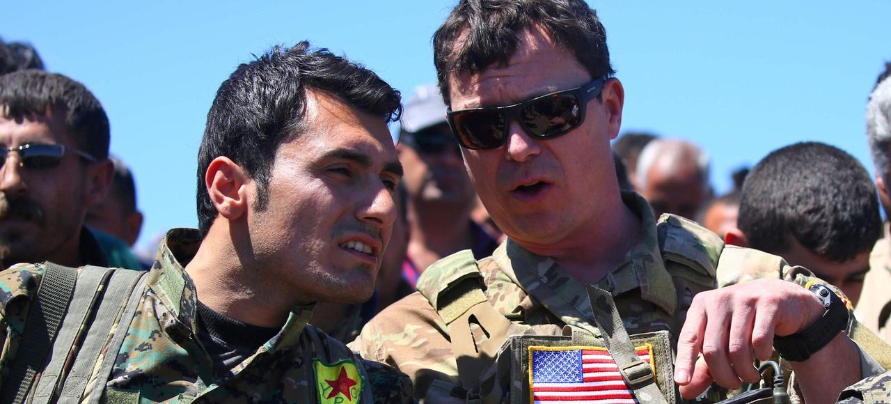Un officier américain de la coalition anti-Daech en discussion avec un combattant kurde des YPG, le 25 avril près de Derik, en Syrie.
