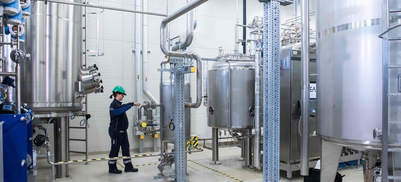 Une ingénieure prélève un échantillon de bactéries durant l'inauguration du démonstrateur industriel de production d'isobutène, le 11 mai, à Leuna.