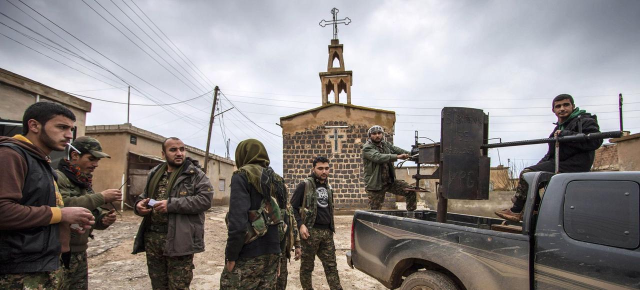 Des combattants kurdes en faction devant l'église du village assyrien de Tel Jumaa, dans la région d'Hassaké, en février 2015.
