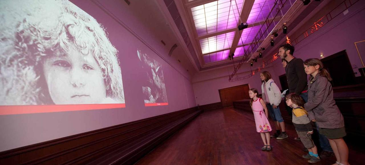 Dans une des salles de l'exposition, une famille assiste à une projection d'images reconstituant les moments forts à bord du navire.