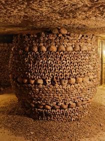 Catacombes de Paris: les ossements rangés figurent un tonneau.