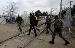 Des soldats macédoniens reconduisent deux migrants à la frontière grecque.