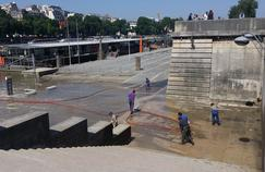 Des services de nettoyage s'affairent au pied de la Tour Eiffel.