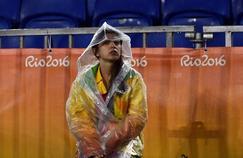 Une bénévole attend sous la pluie.