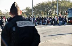 Un gendarme français monte la garde tandis que de jeunes migrants embarquent dans un bus