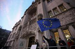 Un homme brandit un drapeau européen, mardi, devant la Cour suprême britannique, à Londres.