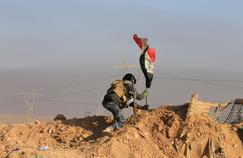 Un membre des forces progouvernementales plante le drapeau irakien durant une bataille avec les djihadistes au sud de Mossoul, ce jeudi.
